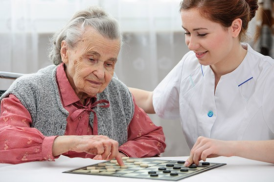 Smiling nurse playing board game with elderly lady