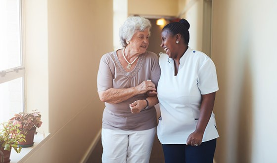 Elderly woman walking closely with nurse while laughing