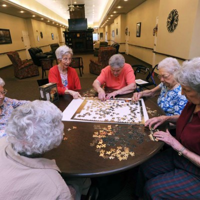 Group of elderly women working on a large jigsaw puzzle together
